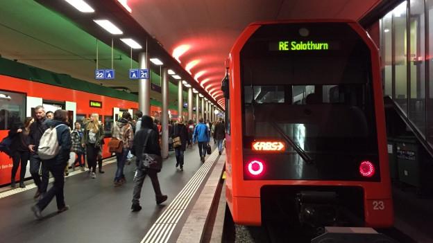 Zug mit Aufschrift Solothurn in Bahnhof mit Pendlern.