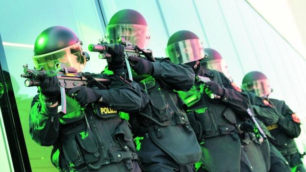 Polizisten in Vollmontur mit Gewehr im Anschlag