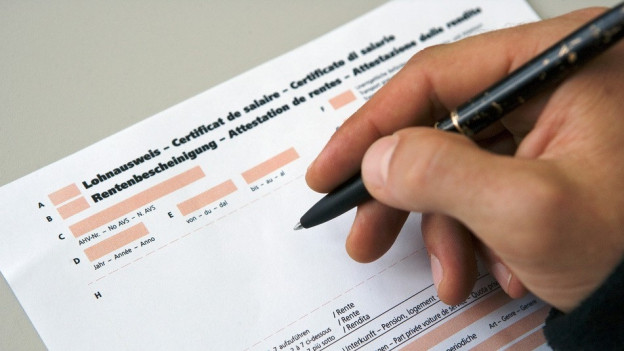 Hand mit Kugelschreiber füllt Lohnformular von Steuererklärung aus.