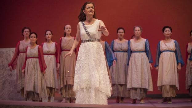 Helena steht im Vordergrund, Chor dahinter.