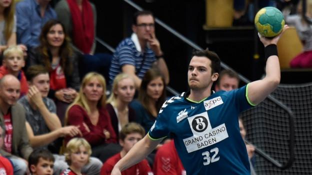 Ein Handballer des TV Endingen in voller Aktion vor Publikum.