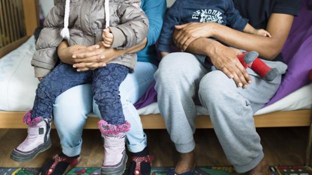 Flüchtlingspaar mit Kindern auf dem Schoss sitzend.