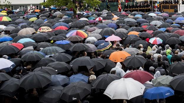 Viele Menschen mit Regenschirmen