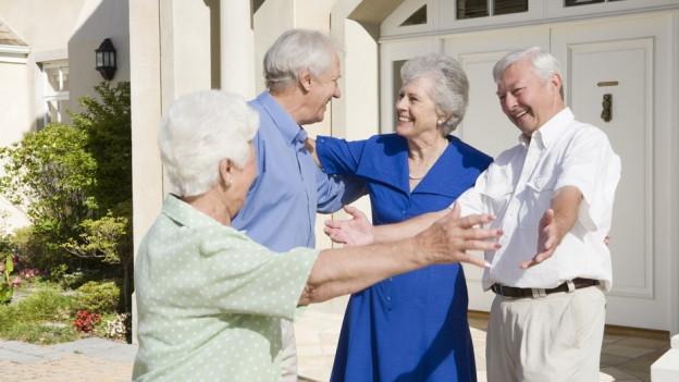 Mehrere Senioren begrüssen sich mit ausgestreckten Armen.