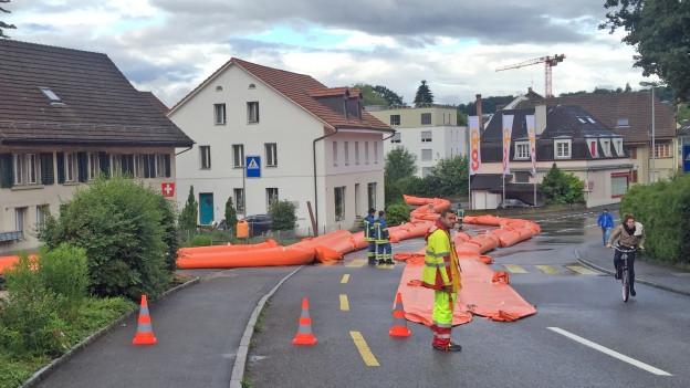 Feuerwehrleute rollen orange Schläuche auf der Strasse zusammen.