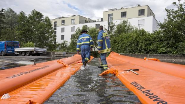 Feuerwehrleute rollen orange Schläuche auf einer Strasse vor einem Wohnquartier ab.