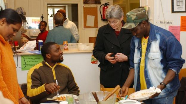 Flüchtlinge und Betreuerin beim Kochen.