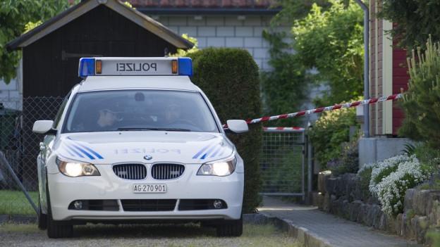 Streifenwagen der Polizei vor abgesperrtem Einfamilienhaus-Grundstück