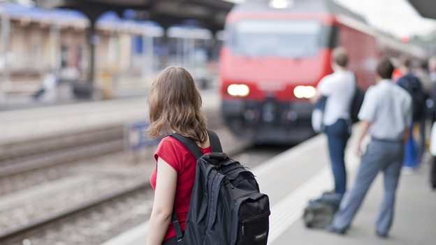 Eine Frau wartet auf einen Zug am Bahnhof.