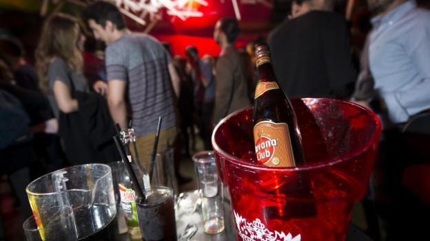 Im Vordergrund Alkoholflasche auf Eiswürfeln. Im Hintergrund Menschen in einer Disco.