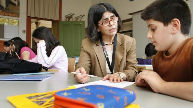 Lehrerin spricht zu Schüler.