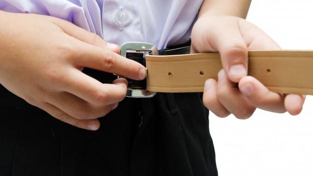 Ein Mann zieht einen Gürtel an.