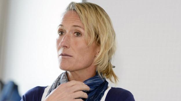 Eine Frau mit blonden Haaren blicjt neben der Kamera vorbei.