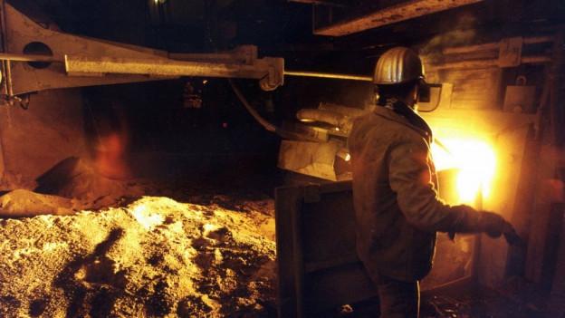 Ein Arbeiter steht vor einem hell leuchtenden Ofen.