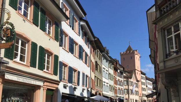 Strasse mit Geschäften, im Hintergrund ein Turm.