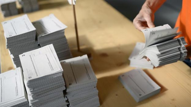 Eine Person blättert durch Abstimmungszettel.