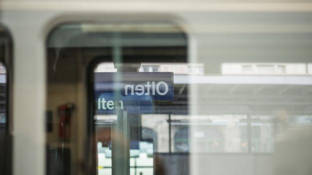 Bahnhofsschild Olten durch Zugfenster gespiegelt.