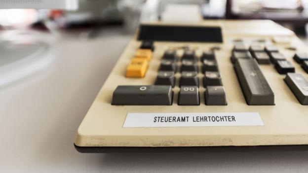 Beiges Telefon mit Aufschrift Steueramt, Lehrtochter.