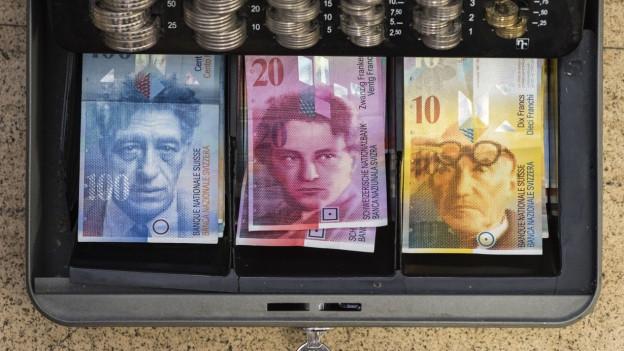 Banknoten und Münzen in einer Kasse.