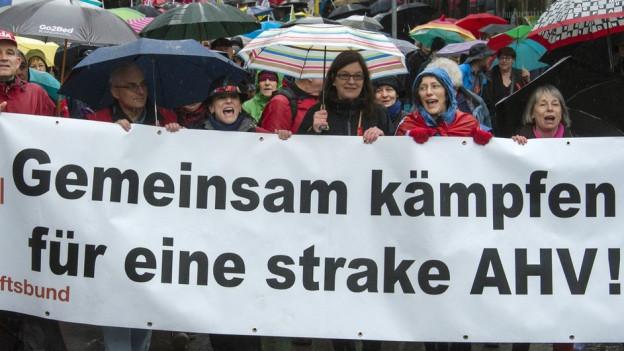 """Menschen halten ein Transparent mit der Aufschrift """"Gemeinsam kämpfen für eine strake AHV""""."""