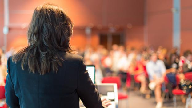 Eine Referentin vor Publikum in einer Halle