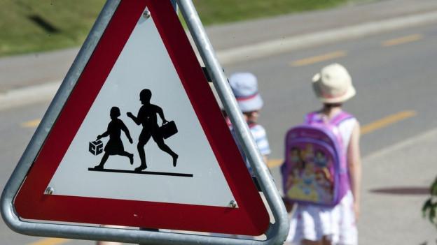Schulweg mit Schülern und Strassenschild.