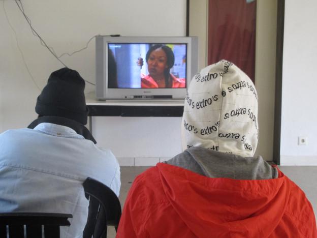Zwei Asylbewerber schauen fern.