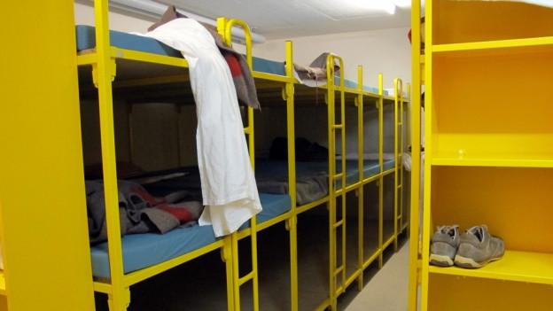 Gelbe Stockbetten in unterirdischer Unterkunft.