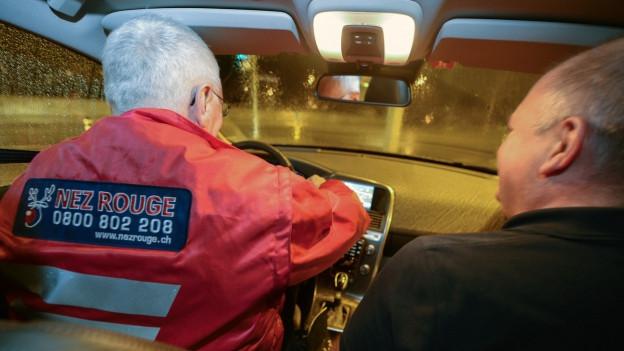 Fahrere mit Nez Rouge-Weste und Mitfahrer in Auto.