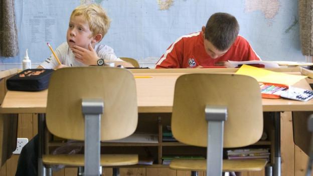 Zwei Kinder an einem Schulpult.