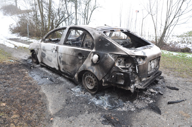 Ein völlig ausgebranntes Auto auf einem Feldweg.