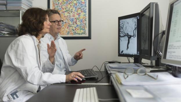 Zwei Ärzte sitzen vor Bildschirmen an einem Pult.