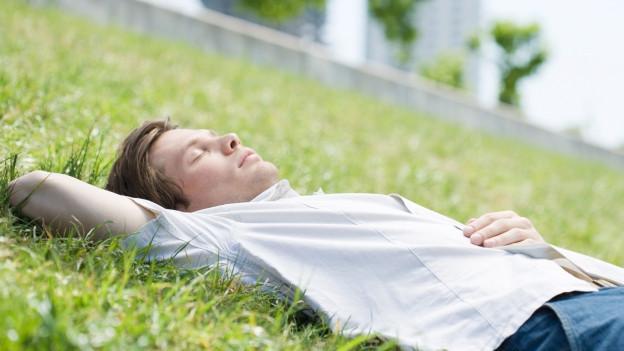 Mann schläft im Gras.