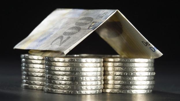 Haus aus Fünffranken-Stücken und einer 200 Franken Note.