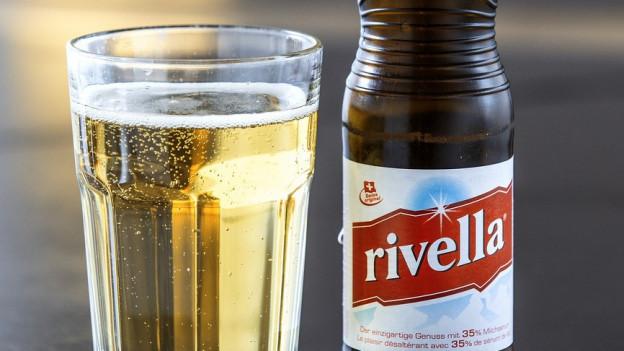Glasflasche und Glas mit Rivella.
