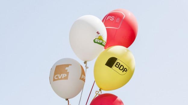 Ballone mit Parteilogos.