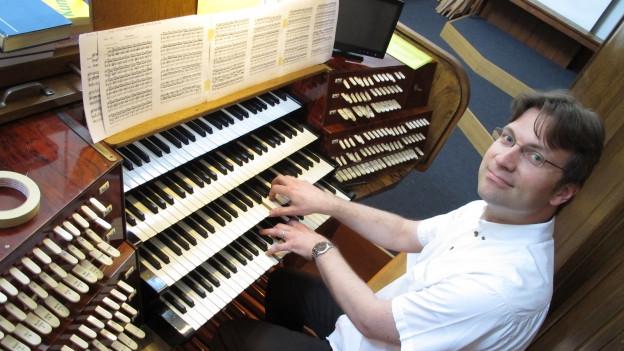 Mann an Orgel.