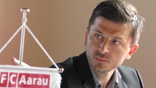 Der neue Trainer hinter einem Wappen des Vereins.