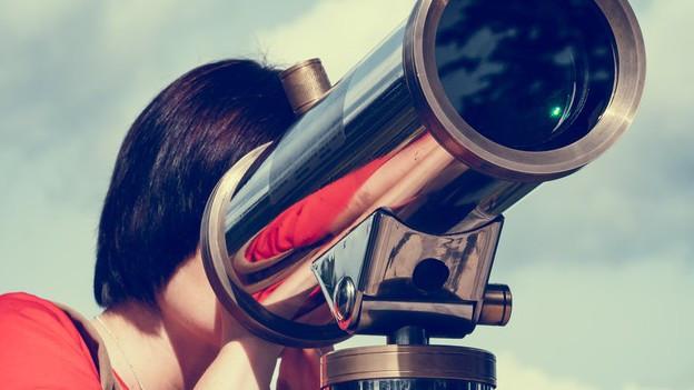 Eine Frau schaut durch eine Fernrohr.