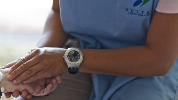 Eine Spitex-Angestellte hält die Hand eines Patienten.