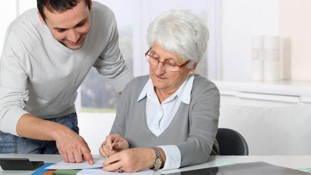 Mann zeigt Seniorin etwas auf Dokument.
