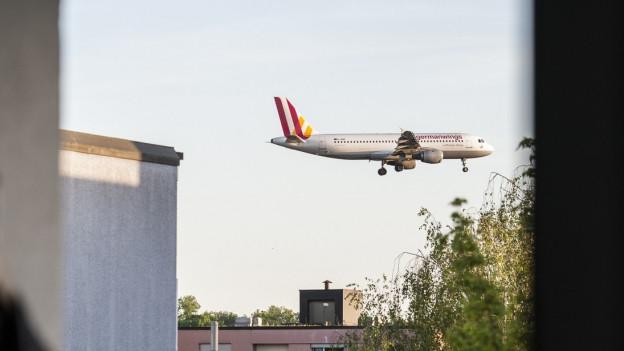 Flugzeug über Häusern in Zürich.