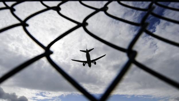 Flugzeug, fotografiert durch einen Maschendrahtzaun