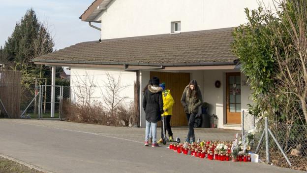 Haus mit Trauerkerzen auf dem Vorplatz