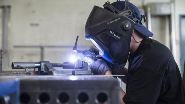 Ein Schweisser in einer Fabrikhalle an der Arbeit