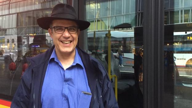 Mann mit Hut vor Postauto.