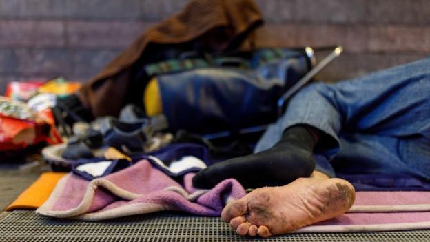 Schmutzige Füsse eines liegenden Menschen auf der Strasse.