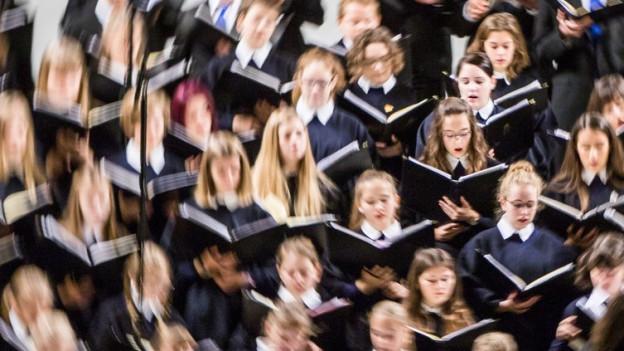 Ein Jugendchor tritt auf.