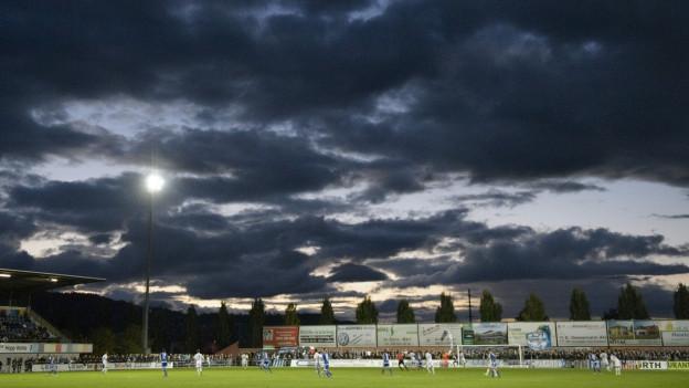 Stadion Niedermatten vor dunklem Himmel.