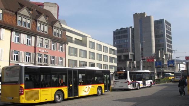 Postauto und Bus in Brugg, im Hintergrund Gebäude der Stadt